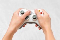 Рука держа gamepad на серой конкретной предпосылке Человек при регулятор играя видеоигру дома Отдых и зрелищность видео стоковая фотография