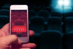 Рука держа smartphone для сдержанно билета кино Стоковое фото RF