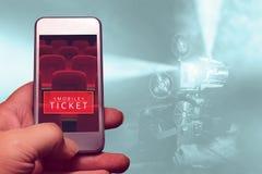 Рука держа smartphone для сдержанно билета кино Стоковое Фото