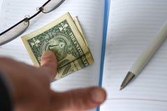 Рука держит деньги в тетради на столе в офисе Давать взятки развращение Доллары для работы работа сделанная на mo стоковая фотография