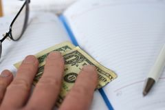 Рука держит деньги в тетради на столе в офисе Давать взятки развращение Доллары для работы работа сделанная на mo стоковое изображение rf