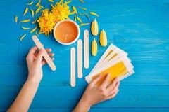 Рука держит деревянную ручку и прокладки для депиляции на голубой деревянной предпосылке стоковое изображение rf