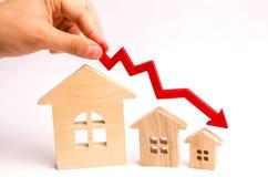 Рука держит красную стрелку над деревянными домами вниз Дома уменьшают Концепция понижаясь спроса и предложение в th стоковое изображение