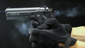 Рука держит огнестрельное оружие изолированный на черноте акции видеоматериалы