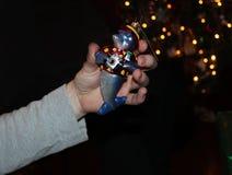 Рука держит орнамент рождественской елки dophin с камерой перед рождественской елкой bokeh стоковые фото