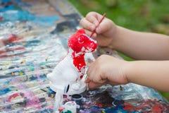 Рука детей покрасила акварель на кукле гипсолита стоковая фотография rf