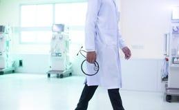 Рука доктора держа стетоскоп с запачканной предпосылкой комнаты спасения терпеливой стоковые изображения