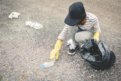 Рука девушки в желтых перчатках выбирая вверх пустую пластмассы бутылки в сумку ящика Стоковые Фото