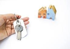 Рука девушки держа ключ дома с деревянным миниатюрным домом Стоковое фото RF