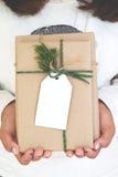 Рука девушки держа ремесло и handmade подарочные коробки подарка на рождество с биркой Стоковое Изображение RF