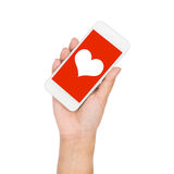 Рука девушки держа сердце дисплея мобильного телефона на красном экране Стоковые Изображения