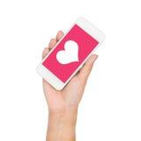 Рука девушки держа сердце дисплея мобильного телефона на розовом экране Стоковые Фотографии RF