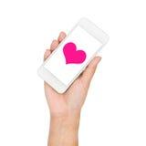 Рука девушки держа сердце пинка дисплея мобильного телефона на экране Стоковая Фотография