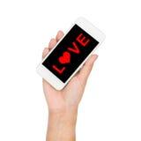 Рука девушки держа текст влюбленности дисплея мобильного телефона на экране Стоковые Фотографии RF
