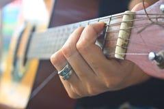 Рука девушки играя акустическую гитару Стоковое фото RF
