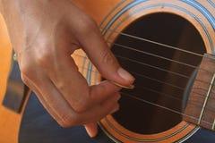 Рука девушки играя акустическую гитару Стоковые Фотографии RF