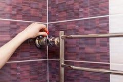 Рука девушки регулирует водопроводный кран в heated рельсе полотенца стоковое изображение