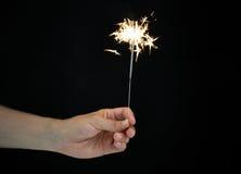 Рука держа бенгальский огонь над черной предпосылкой Стоковая Фотография