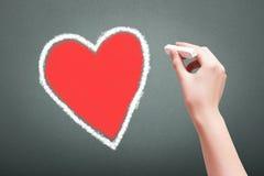 Рука держа белое сердце чертежа мела Стоковая Фотография RF