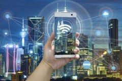 Рука держа белый телефон с scape города Стоковое Изображение RF