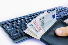 Рука держа бумажник с деньгами на клавиатуре Стоковые Фотографии RF