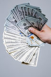 Рука держа вентилятор денег 100 долларовых банкнот на серой предпосылке Банкнота, конец-вверх Предложение взятки Стоковая Фотография