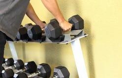 Рука держа гантель в спортзале стоковая фотография rf