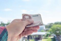 Рука держа деньги на предпосылке дома нерезкости Стоковые Фотографии RF