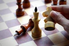 Рука держа деревянный комплект шахмат на шахматной доске Шахмат Чернота и w Стоковая Фотография