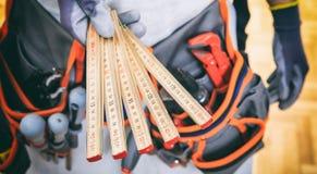 Рука держа деревянный метр стоковые фото