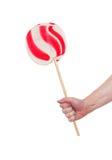 Рука держа леденец на палочке тросточки конфеты Стоковые Фото
