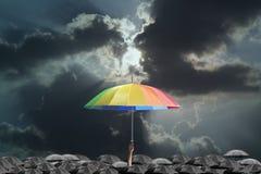 Рука держа зонтик радуги Стоковая Фотография