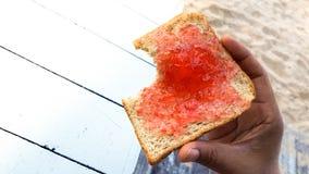 Рука держа здравицу укуса с бататом клубники около песка Стоковое Изображение