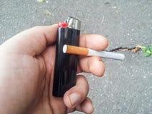 Рука держа лихтер и сигарету Стоковое фото RF