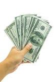 Рука держа, который дуют пригоршню долларовых банкнот Стоковые Изображения RF