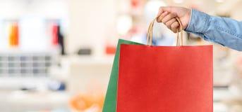 Рука держа красную хозяйственную сумку на предпосылке магазина нерезкости, знамени w Стоковые Изображения RF