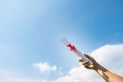 Рука держа крен сертификата градации под солнечностью, голубой Стоковые Изображения