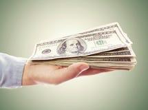 Рука держа кучу наличных денег Стоковые Изображения