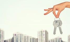 Рука держа ключи и здания на белизне Стоковые Фотографии RF