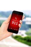 Рука держа мобильный телефон с номером службы экстренной помощи 911 Стоковое фото RF