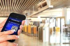 Рука держа мобильный телефон с передвижным шагом восхождения на борт Стоковая Фотография