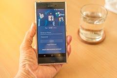 Рука держа мобильный телефон с применением Facebook Стоковая Фотография