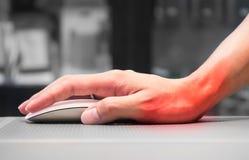 Рука держа мышь компьютера имея боль запястья руки стоковое изображение rf