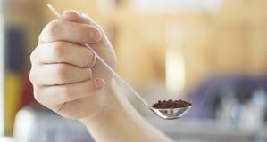 Рука держа ложку кофе Стоковые Фотографии RF