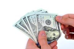 Рука держа 100 долларов на белой предпосылке Стоковое Фото