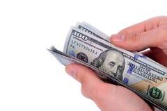 Рука держа 100 долларов на белой предпосылке Стоковая Фотография RF