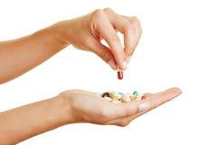 Рука держа пилюльку над медициной стоковое изображение