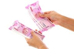 Рука держа 2000 примечаний рупии против белизны Стоковое Изображение RF