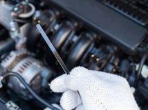 Рука держа проверку уровня смазки автомобиля Стоковые Изображения