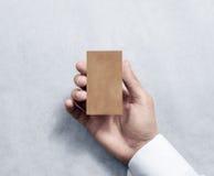 Рука держа пустой вертикальный модель-макет дизайна визитной карточки kraft Стоковая Фотография